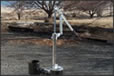Hand water pump in yard.